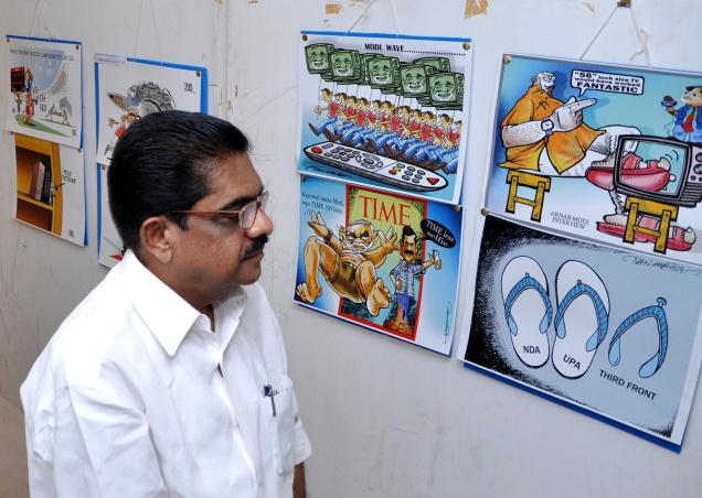 KPCC president V.M. Sudheeran enjoys the political cartoon exhibition organised by the Ernakulam Press Club at Kochi on Wednesday. /  The Hindu