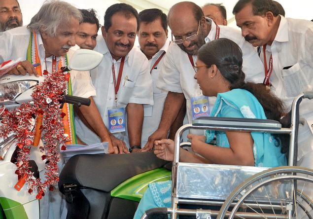 Mary Shahina receives a modified scooter from Chief Minister Oommen Chandy on Friday.— Photo: Thulasi Kakkat